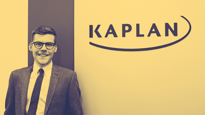 Young student next to Kaplan sign