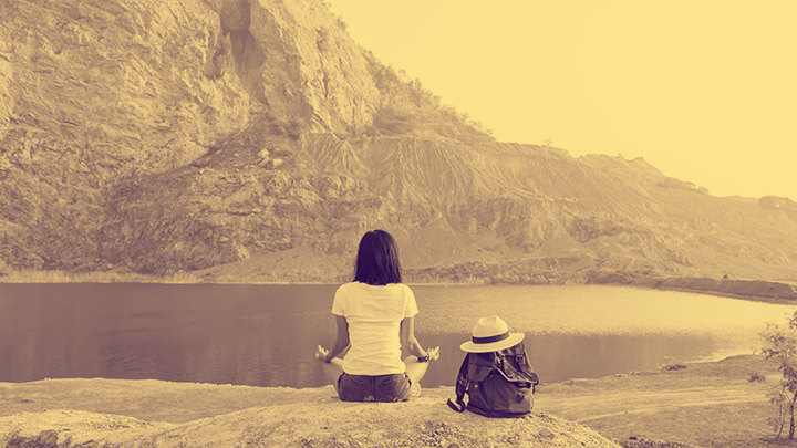 A woman sat meditating in front of a scenic lake and mountain, with her backpack to one side with a sun hat on top