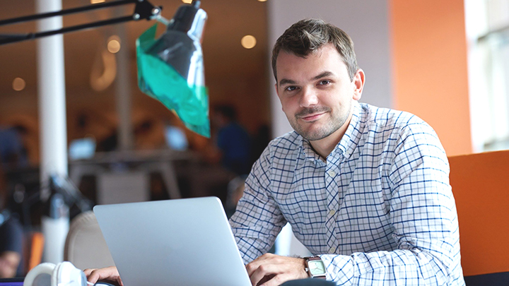 Man working at laptop, smiling at camera