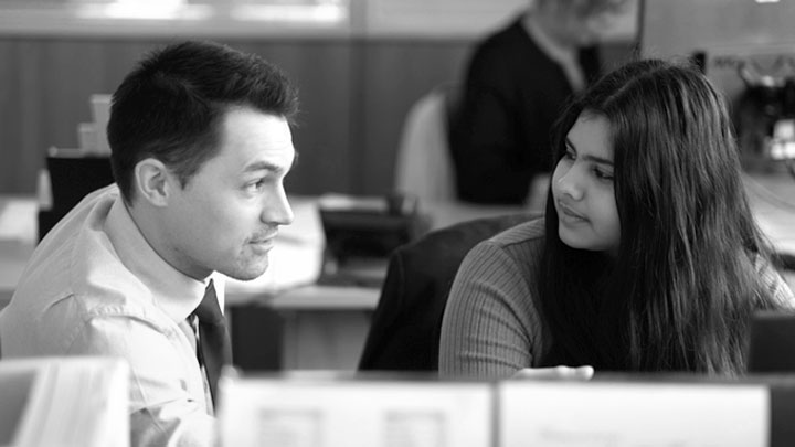 A man and a woman talking at a desk in an office