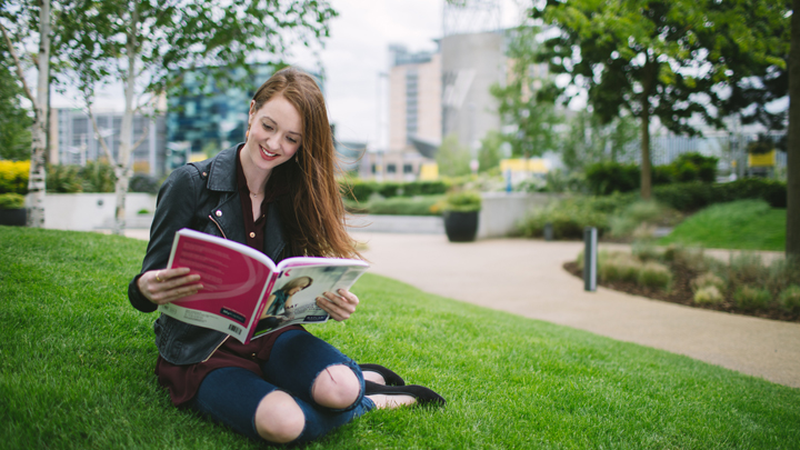 A woman sitting on grass reading a Kaplan study text.