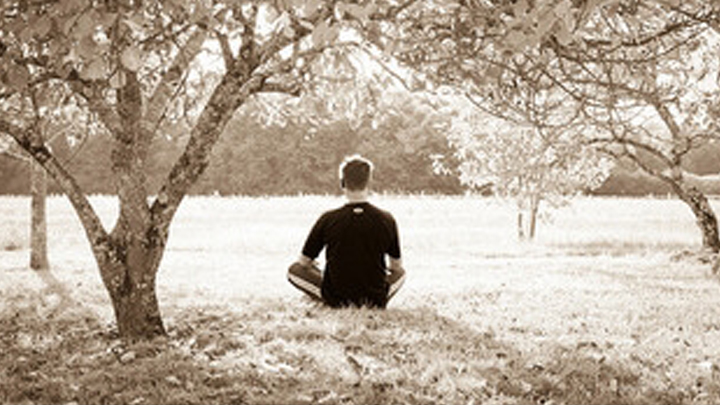 A man meditating while sitting on grass surrounded by trees.