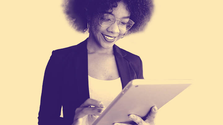 Woman smiling at handheld tablet computer