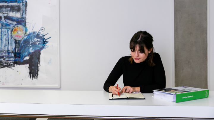 A woman sitting at a desk writing in a notebook