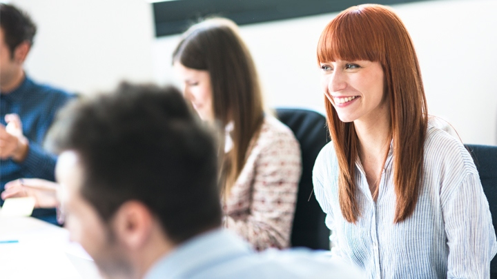 Red headed woman smiling in classroom