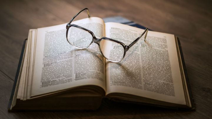 An open book with a pair of spectacles on it.