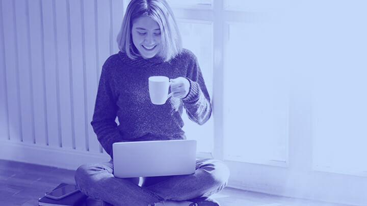 Student sat on floor with laptop and mug in hand, smiling