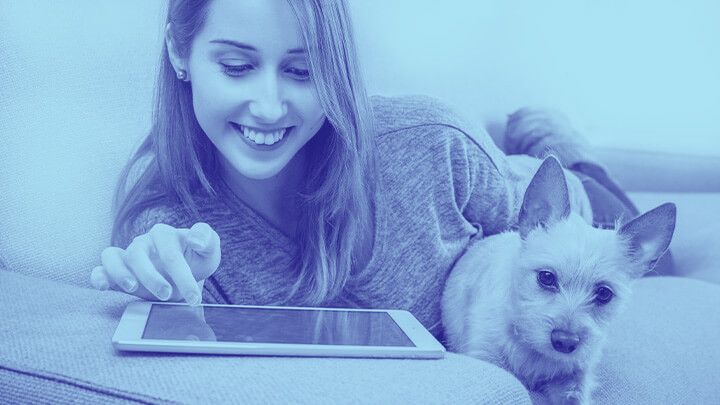 Woman working on tablet computer with dog beside her