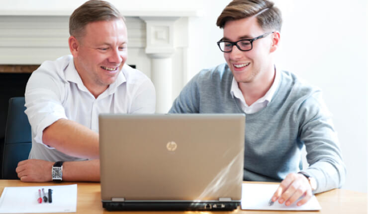 An apprentice and his employer looking at something on a laptop