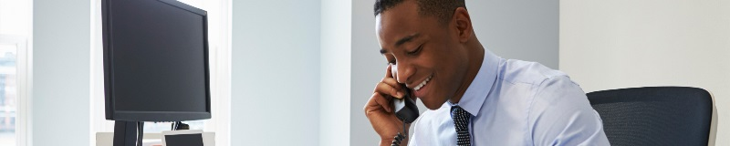 Man talking on his desk phone