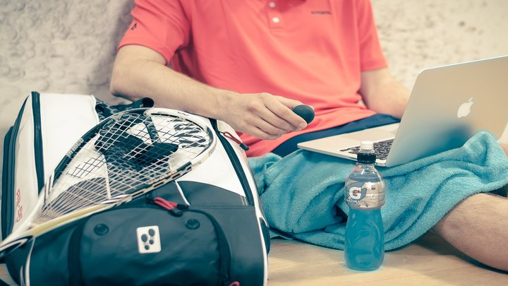 A tennis player looking at a laptop with a tennis racket resting on a sports bag
